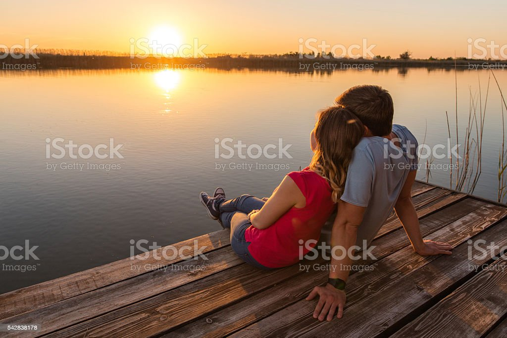 Romantic couple in love enjoying by the lake at sunset. stock photo