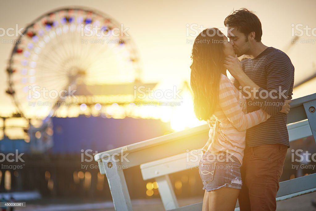 romantic couple kissing at sunset stock photo