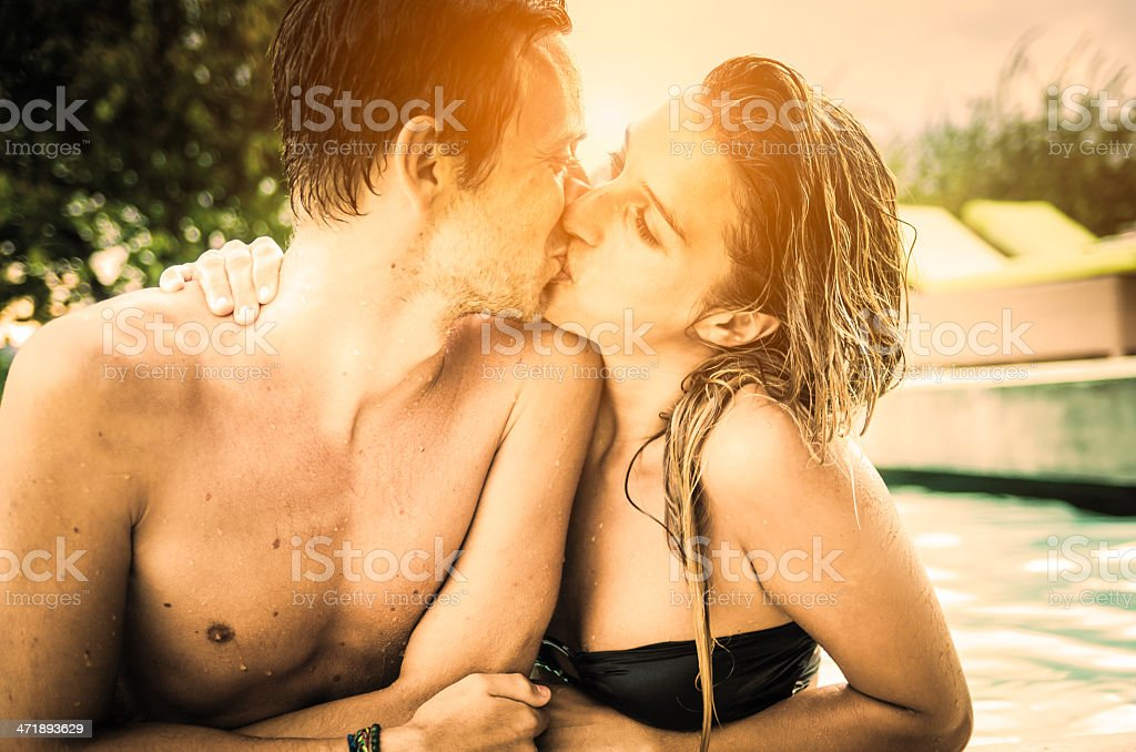 Romantic couple kissing in the swimming pool stock photo