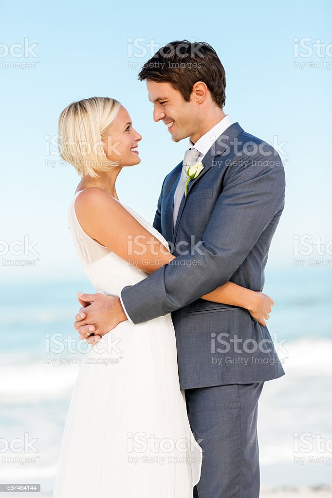 Romantic Couple Looking At Each Other On Beach stock photo
