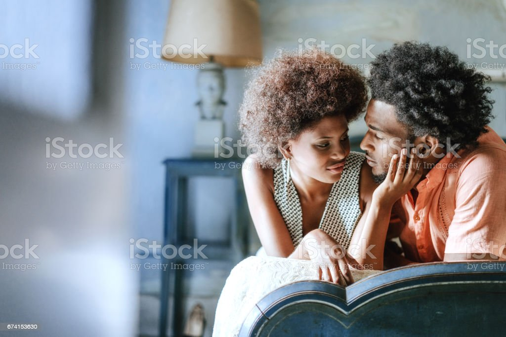 Romantic couple looking at each other while relaxing on bed at home stock photo