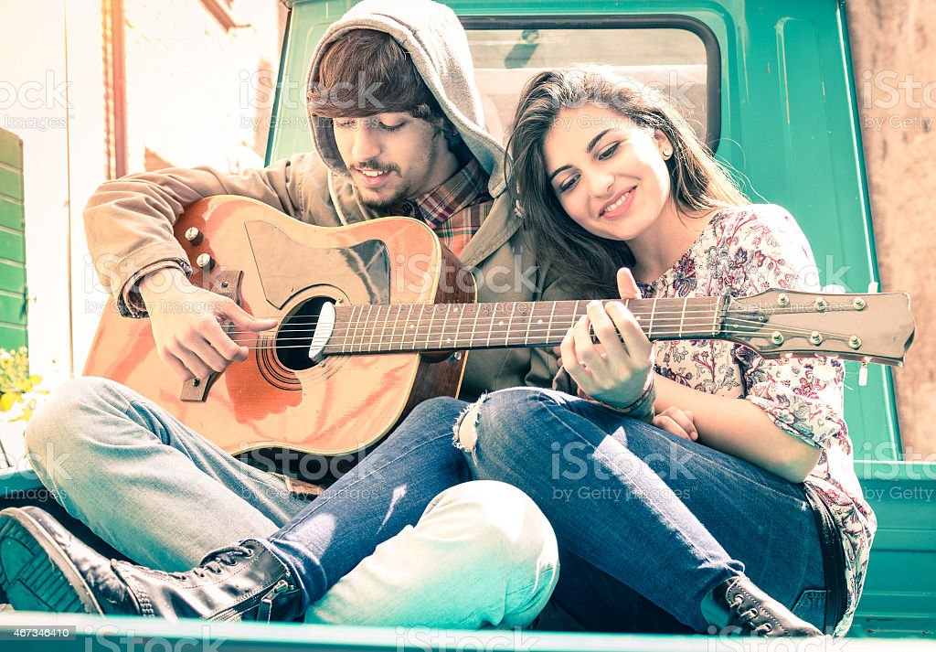 Romantic couple of lovers playing guitar on old fashioned minicar stock photo