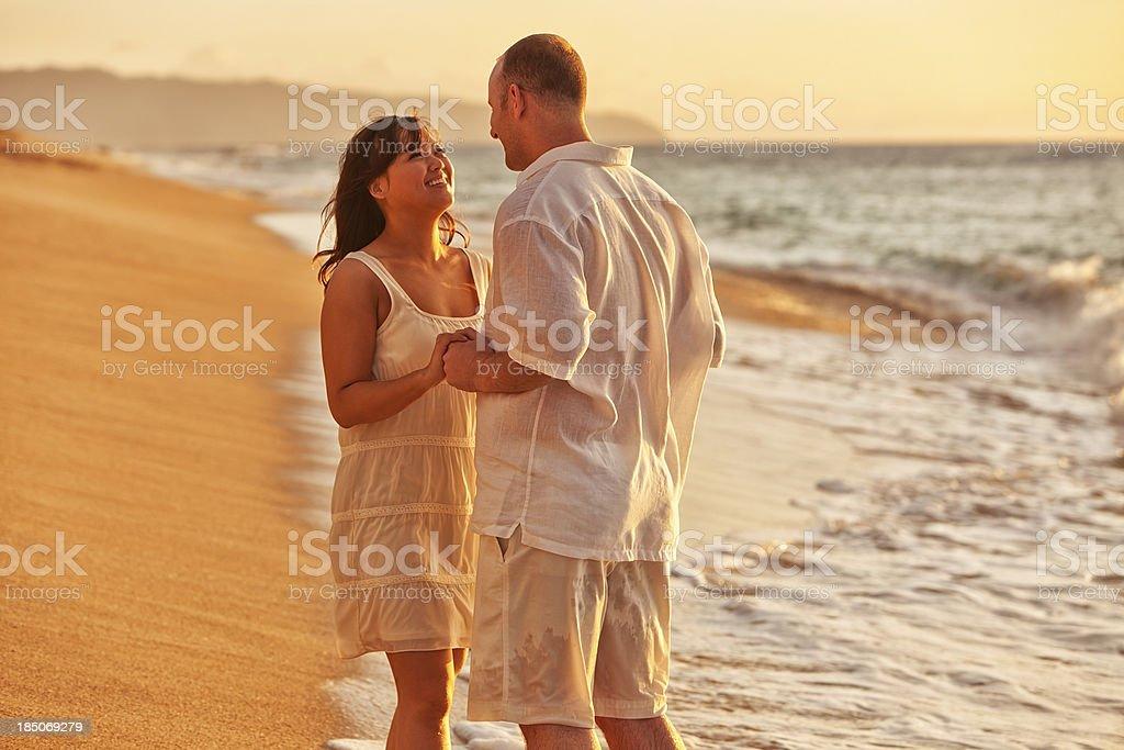 Romantic Couple on Hawaiian Beach at Sunset stock photo