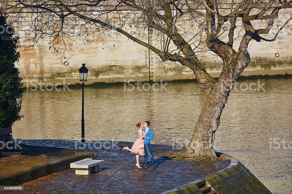Romantic couple on the Seine embankment in Paris, France stock photo