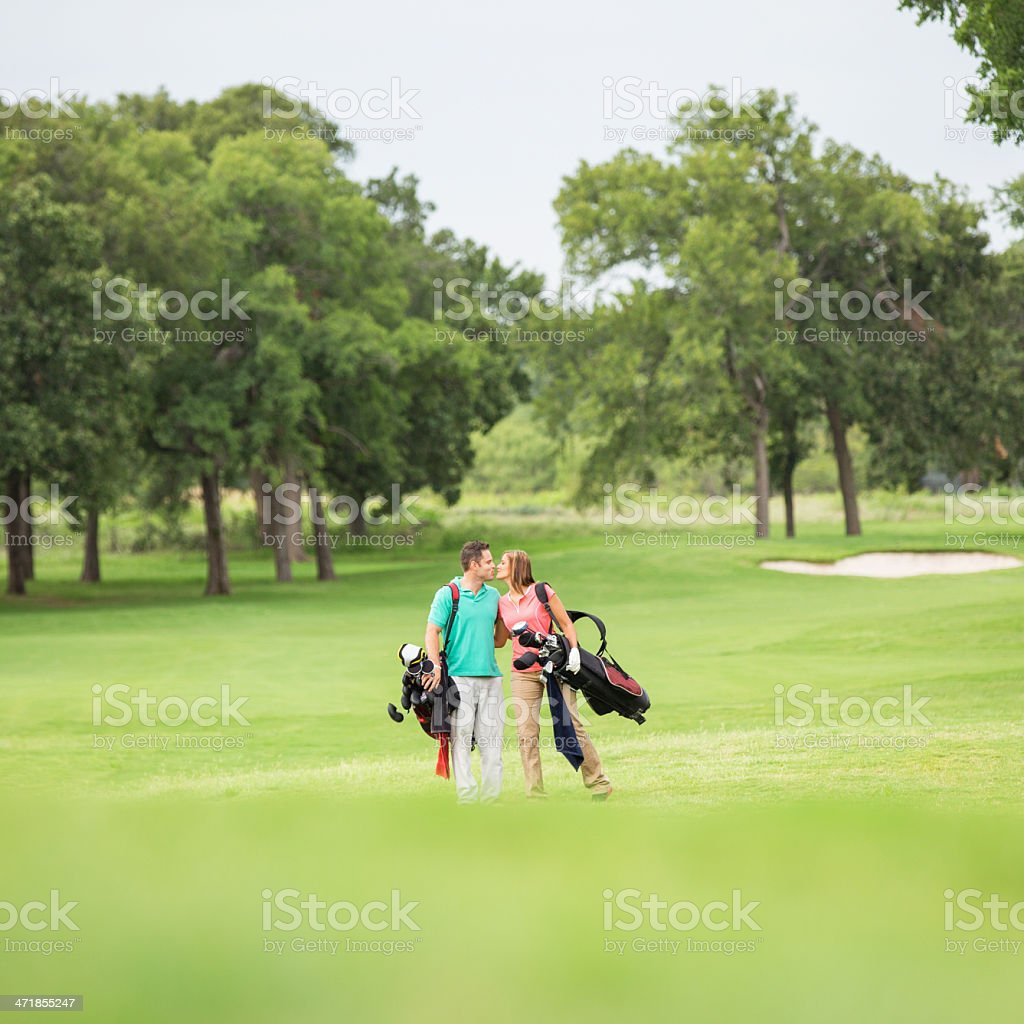 Romantic couple playing golf together on green course stock photo