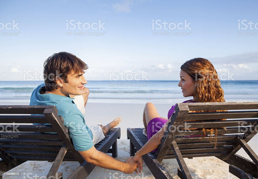 Romantic couple sitting by the beach royalty-free stock photo