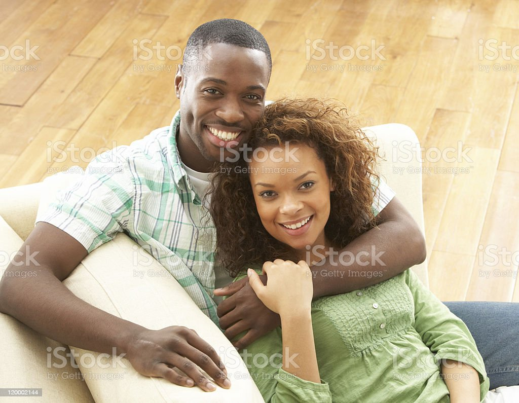 Romantic couple sitting comfortably on a sofa stock photo