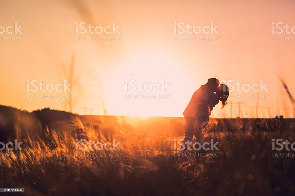 Romantic couple standing and kissing on background summer meadow sunset stock photo