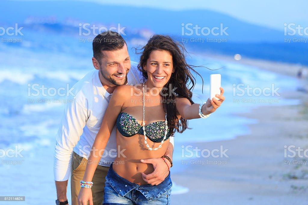 Romantic couple taking selfie on the beach stock photo