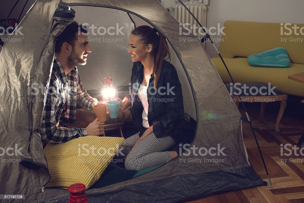 Romantic couple talking to each other during camping at home. stock photo