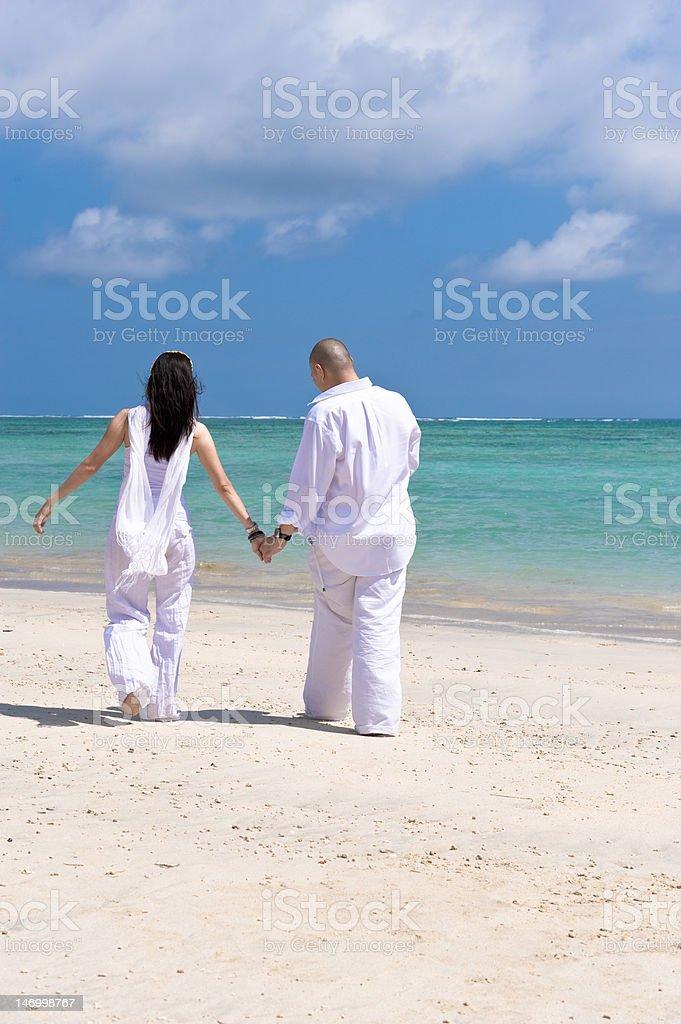 romantic couple walking on the beach royalty-free stock photo