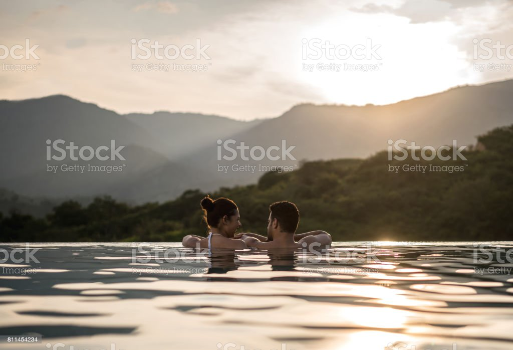 Romantic couple watching the sunset in the swimming stock photo