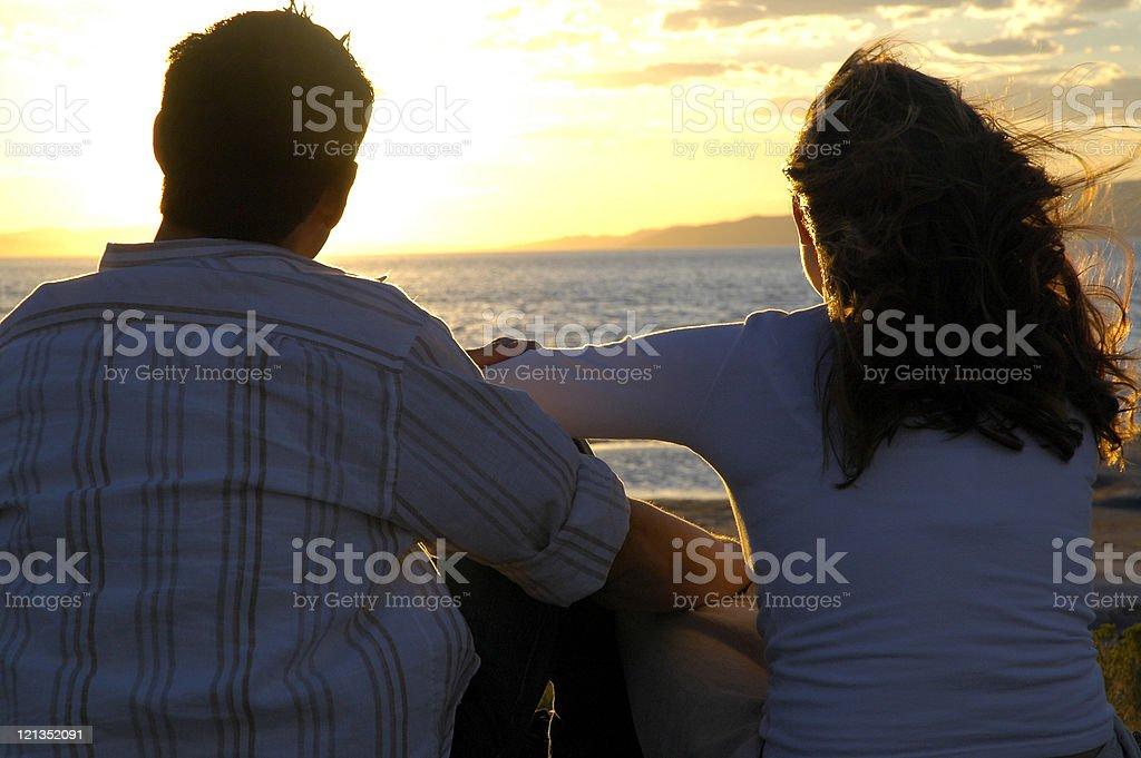 Romantic couple watching the sunset stock photo