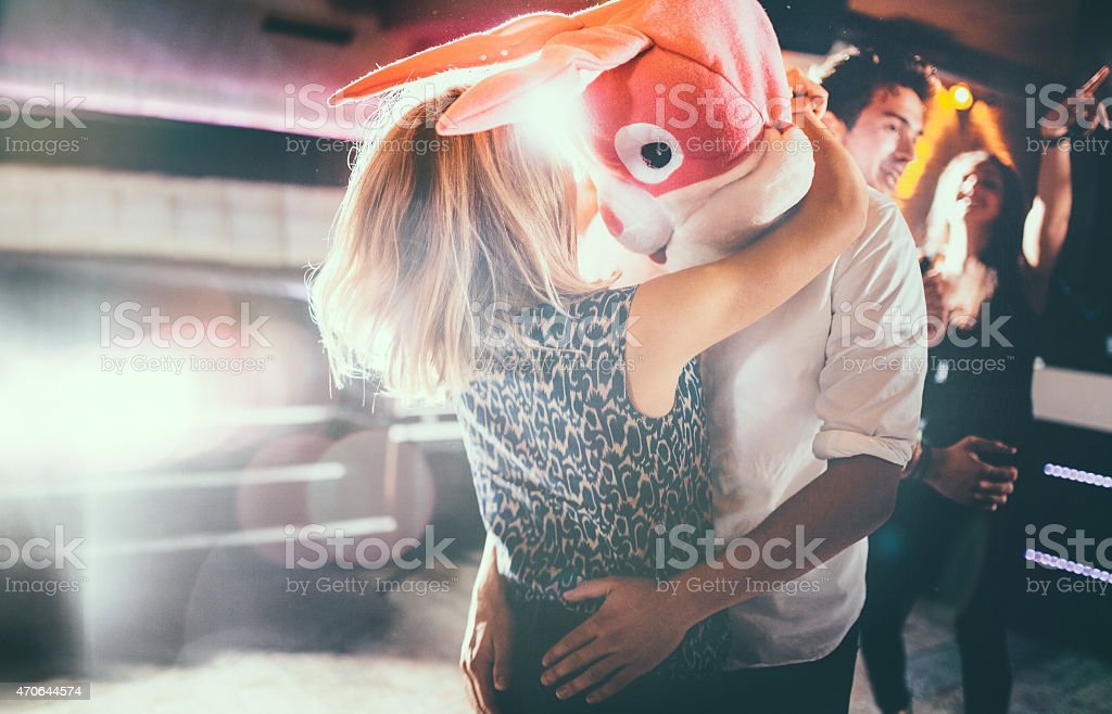 Romantic couple, with guy in a bunny head dancing together stock photo