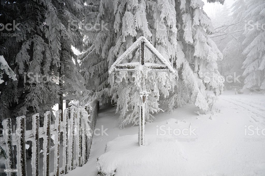 romantic crucifix in the snowy winter forest stock photo