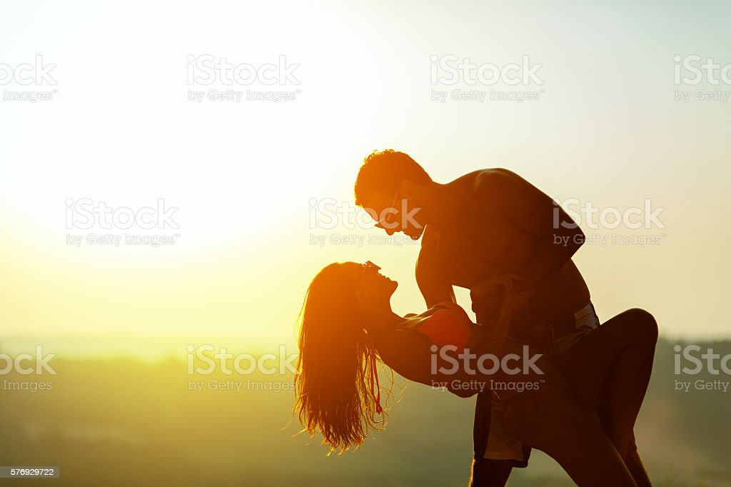 Romantic dance at sunset by couple stock photo