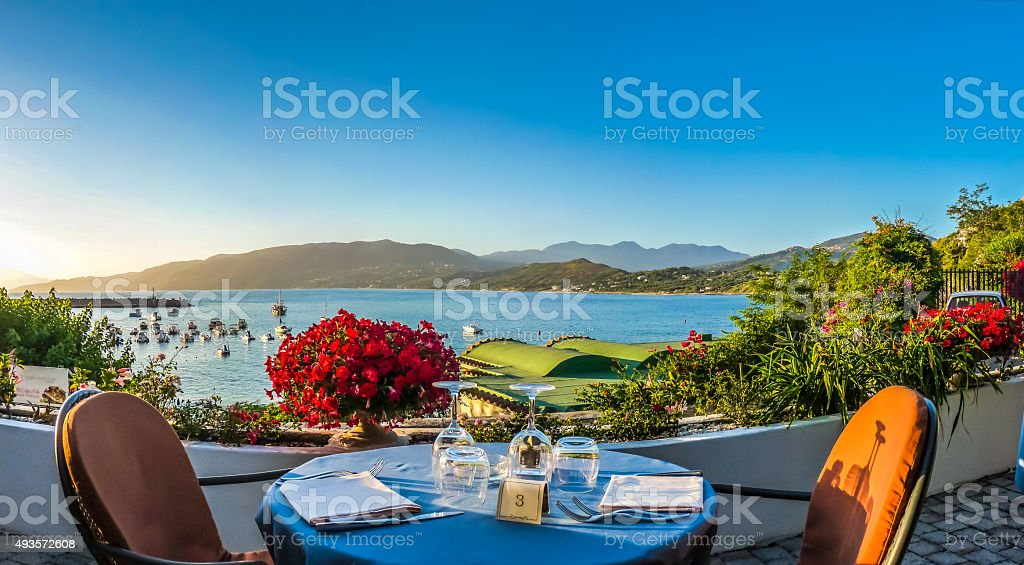 Romantic dinner place with idyllic view of coastscape at sunset stock photo