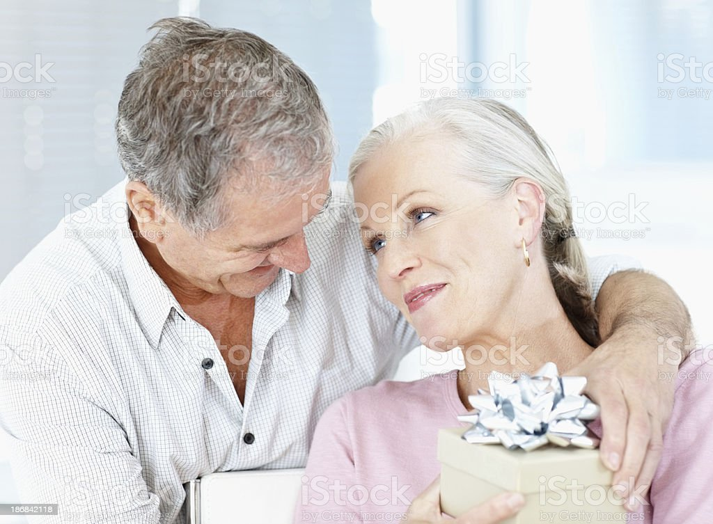 Romantic elderly man giving a giftbox to his wife stock photo