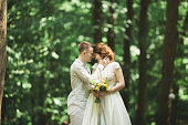 Romantic, fairytale, happy newlywed couple hugging and kissing in a