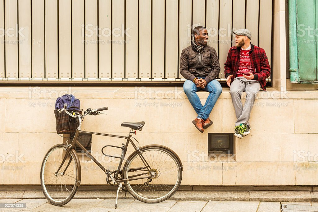 Romantic Gay Hipster Couple Sitting Together Talking stock photo