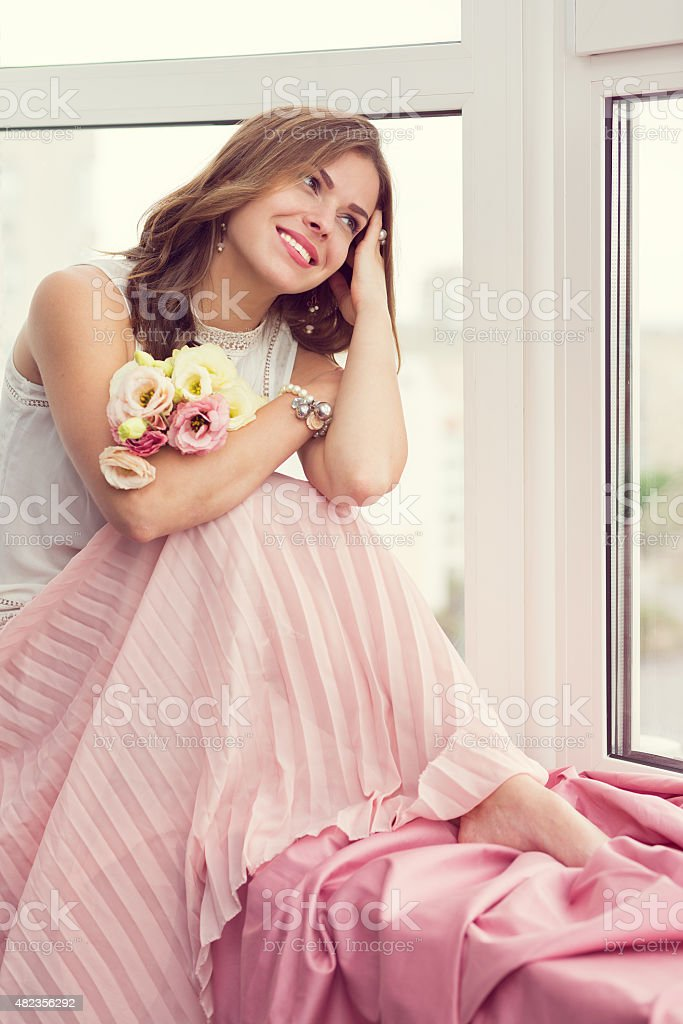 Romantic girl sitting by the window stock photo
