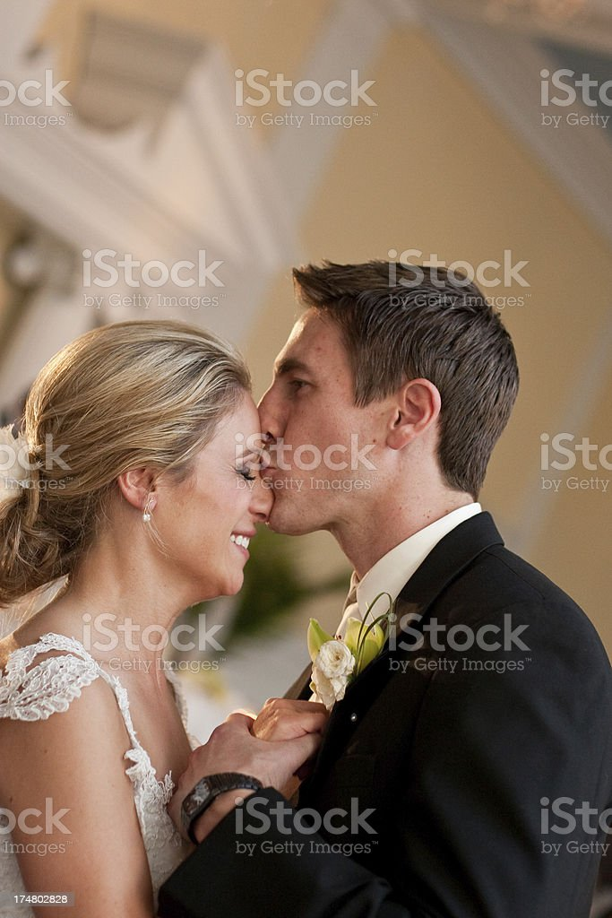Romantic Groom is Kissing his Beautiful Bride in Reception Hall royalty-free stock photo