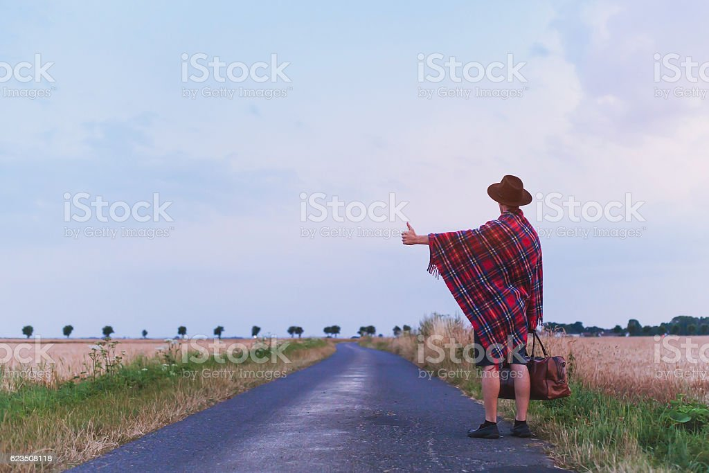 romantic hippie man travels by hitchhiking stock photo