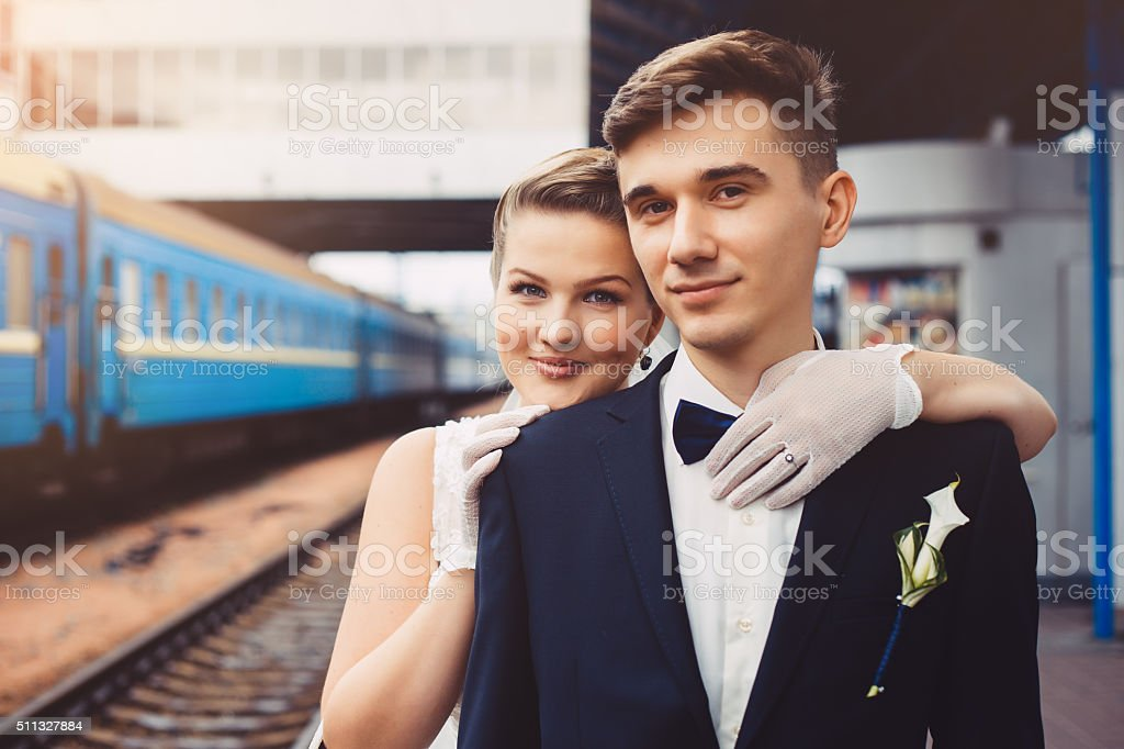 Romantic hugs of newlyweds and train in the background stock photo