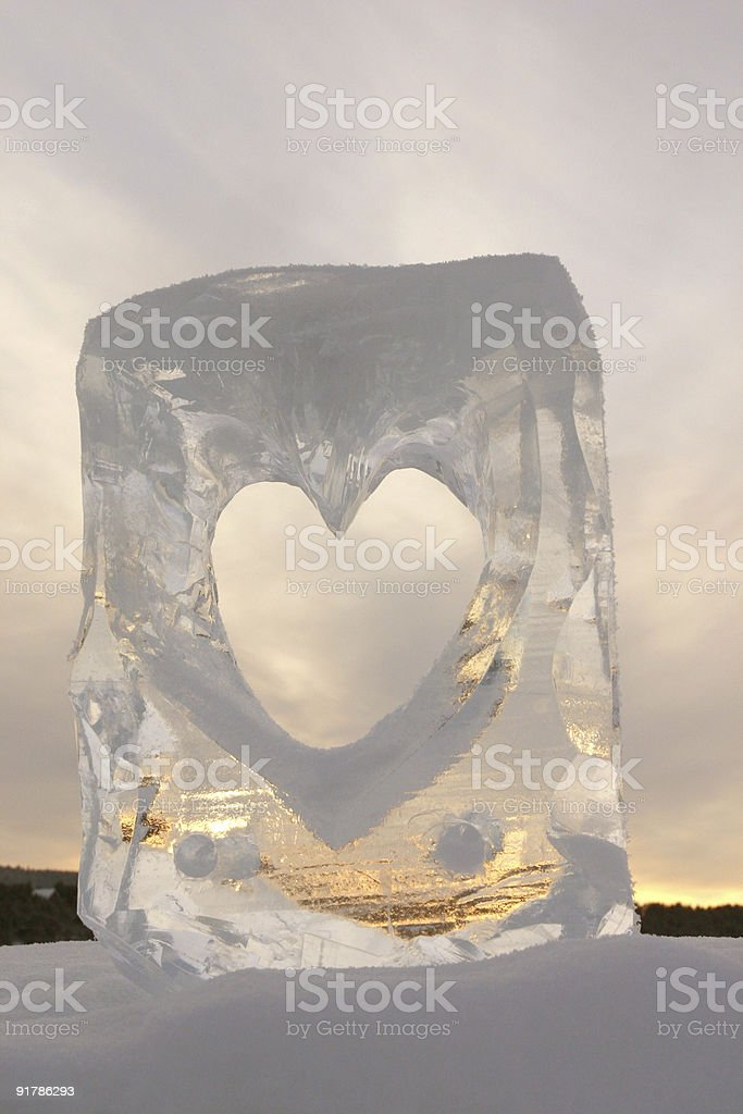 romantic love heart carved in ice against a cloudy sky stock photo