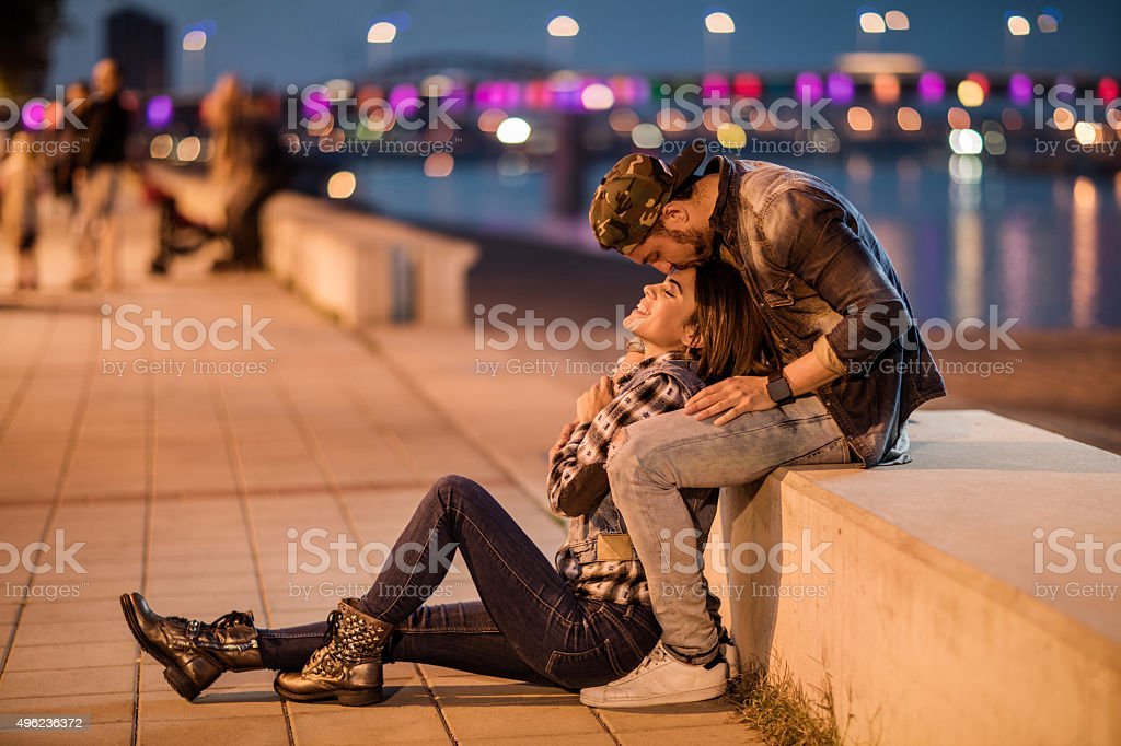 Romantic man kissing his girlfriend on a forehead at riverside. stock photo