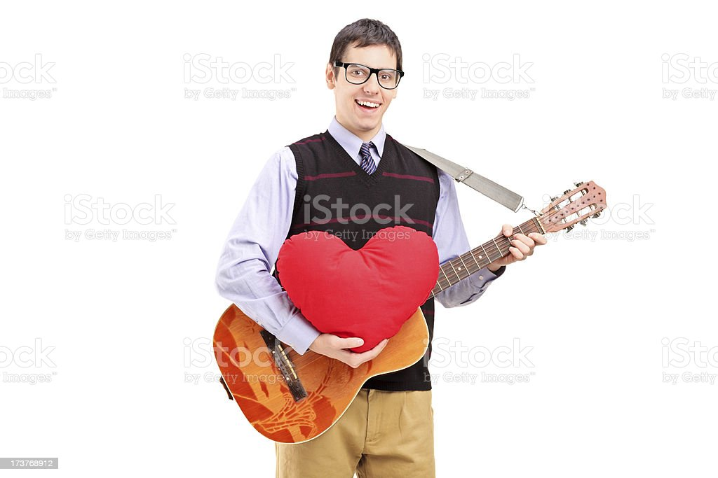 Romantic man playing a guitar and holding red heart royalty-free stock photo