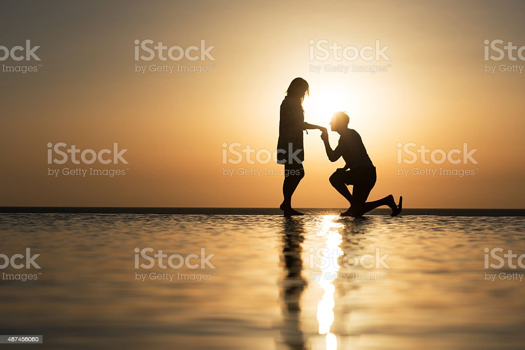 Romantic marriage proposal on infinity pool at sunset. stock photo