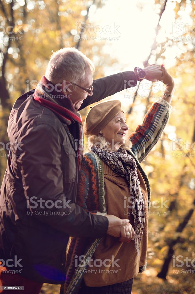 Romantic mature couple dancing while enjoying a day in nature. stock photo