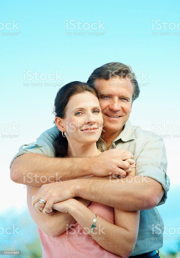 Romantic mature couple embracing against blue sky stock photo