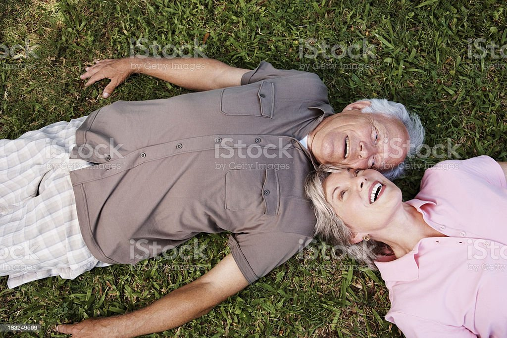 Romantic mature couple relaxing on grass royalty-free stock photo