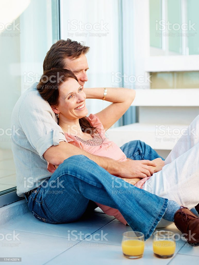 Romantic mature couple relaxing with drinks at home stock photo
