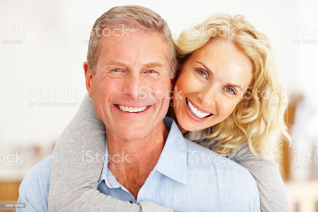 Romantic mature woman embracing man from behind royalty-free stock photo