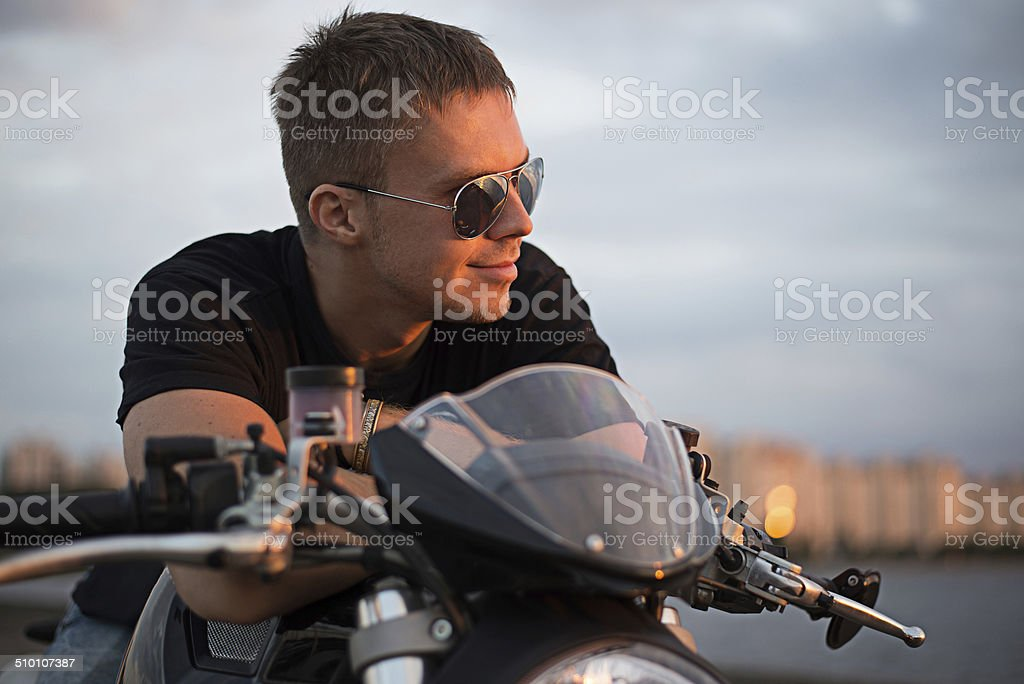Romantic portrait handsome biker man on a bike stock photo