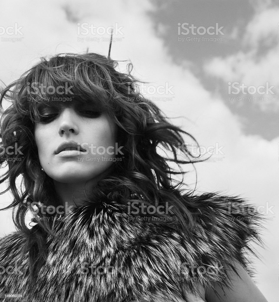 Romantic portrait of young woman in fur with sky stock photo