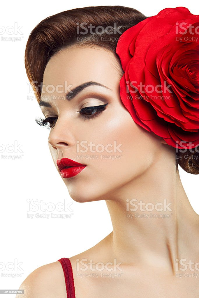 Romantic portrait of young woman with a red rose on her hair stock photo