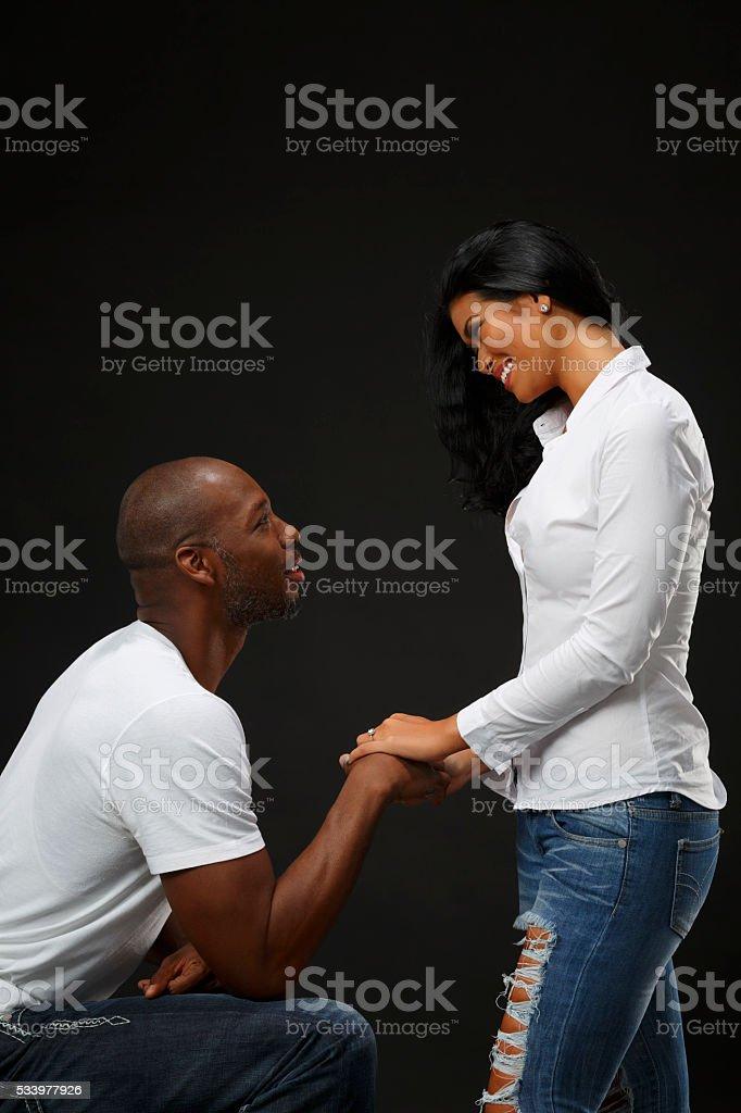 Romantic proposing  Kneeling man gentlelman holding woman's hand stock photo