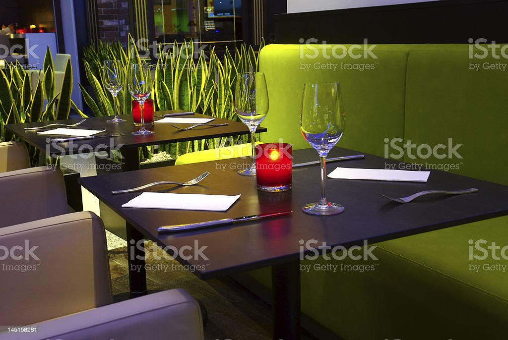 Romantic restaurant environment tables with lit candles stock photo