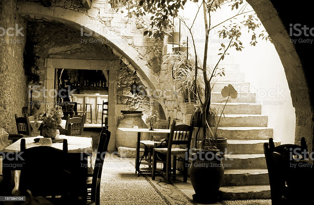 Romantic restaurant interior in Greece, wooden tables, chairs, sepia toned royalty-free stock photo