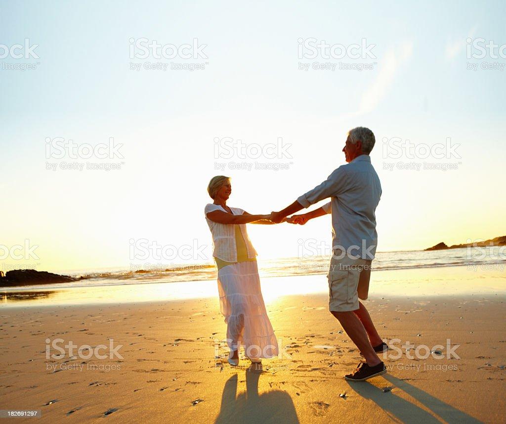 Romantic retired couple enjoying together on beach royalty-free stock photo