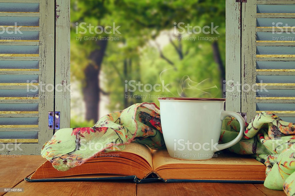 romantic scene of cup of coffee next to old book stock photo