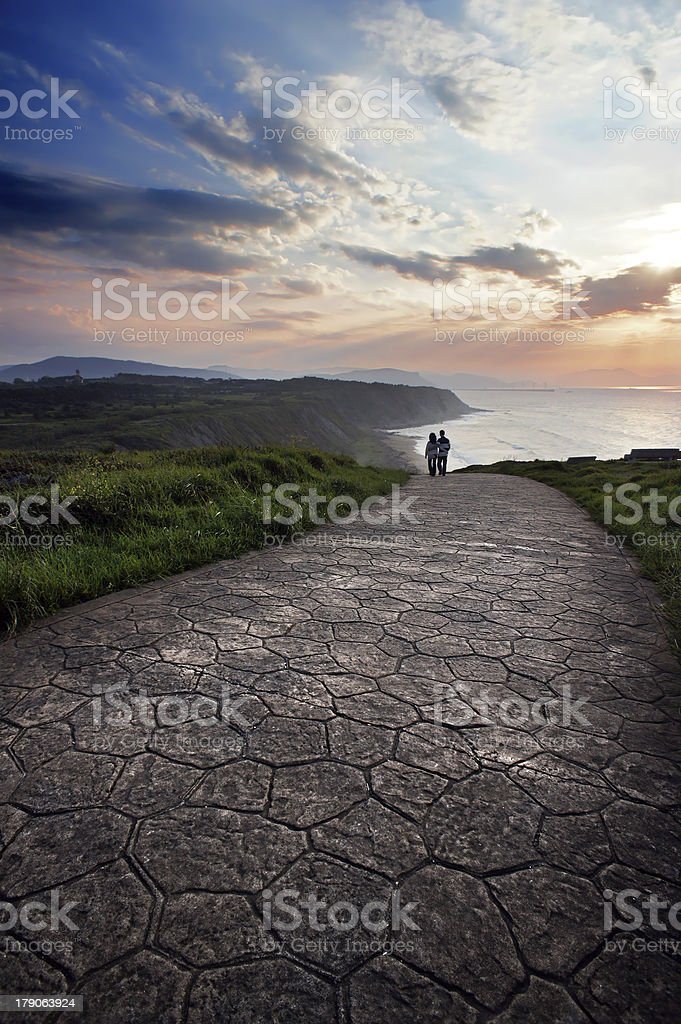 romantic scene of two person walking at sunset stock photo