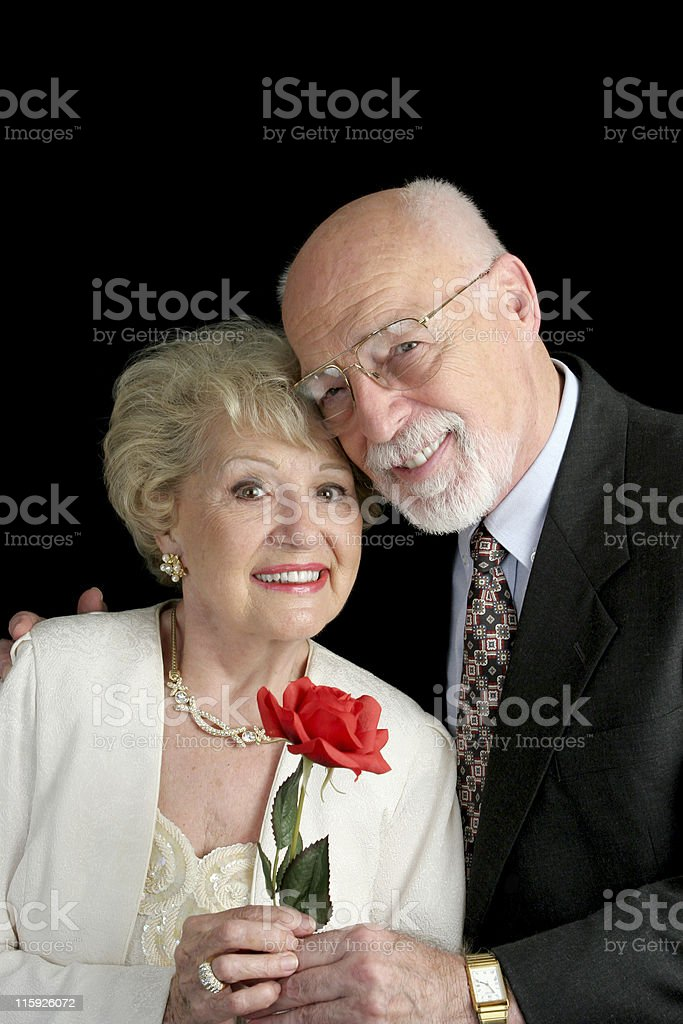 Romantic senior couple in formal clothes holding a red rose stock photo