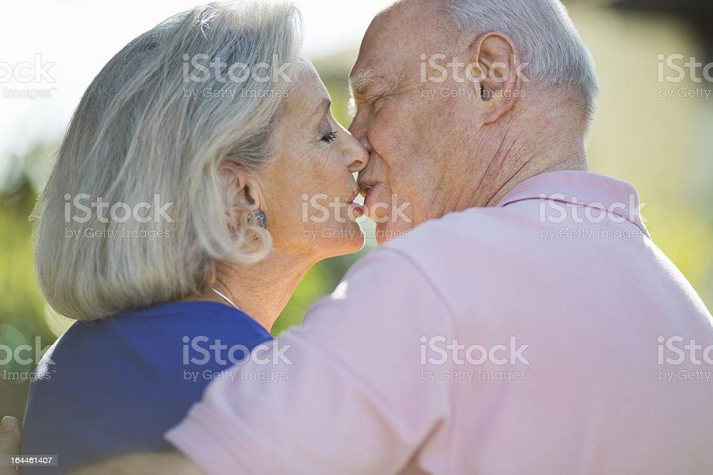 Romantic Senior Couple Kissing In Park royalty-free stock photo