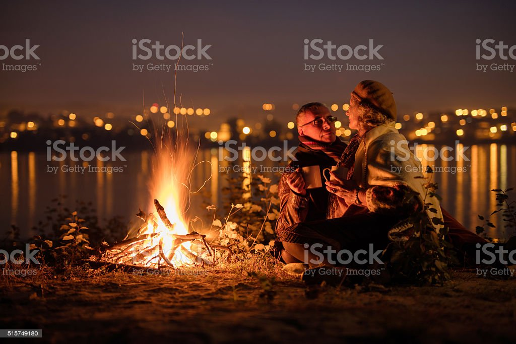 Romantic senior couple relaxing in the night by the fire. stock photo