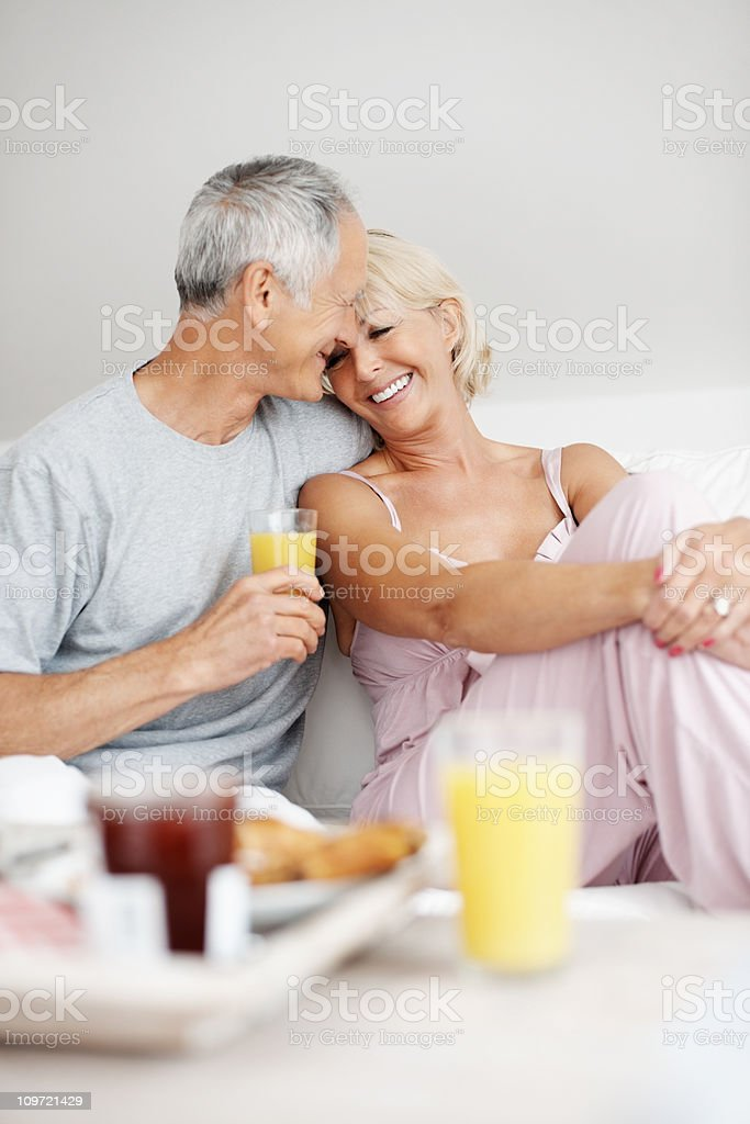 Romantic senior man sitting with wife on sofa at home royalty-free stock photo